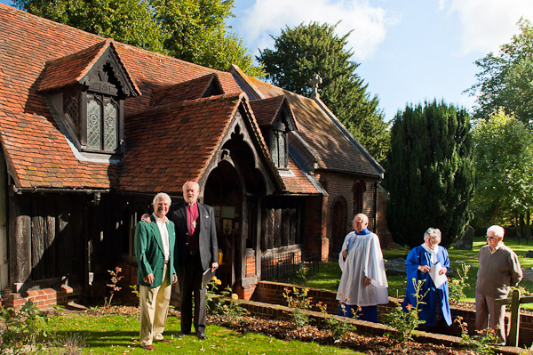 The Rt Hon and Rt Revd Bishop of London in front of Greensted Church, the oldest wooden church in the world