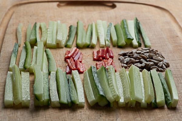 Cucumbers, chilli, sunflower seeds on a chopping board