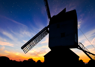Picture of a windmill in front of a fiery sunrise and a star-filled night sky