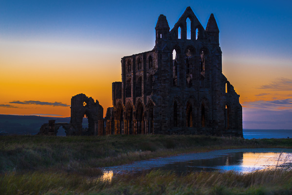 Picture of Whitby Abbey in front of the setting sun