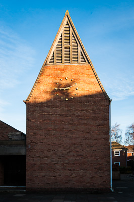 Picture of a church spire, with the top triangular bit fully sunlit and the bottom rectangular bit in shadow.