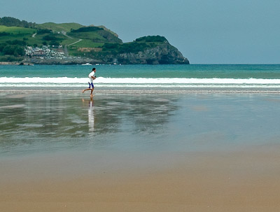 A jogger running on the beach in Cantabria, Spain