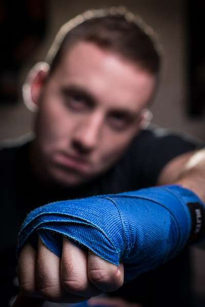 Image with focus on an outstretched fist with the boxer's face behind out of focus