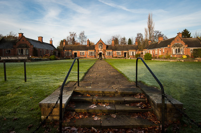 Picture of an almshouse, with a stone path forming a triangle leading the eye to the house entrance.